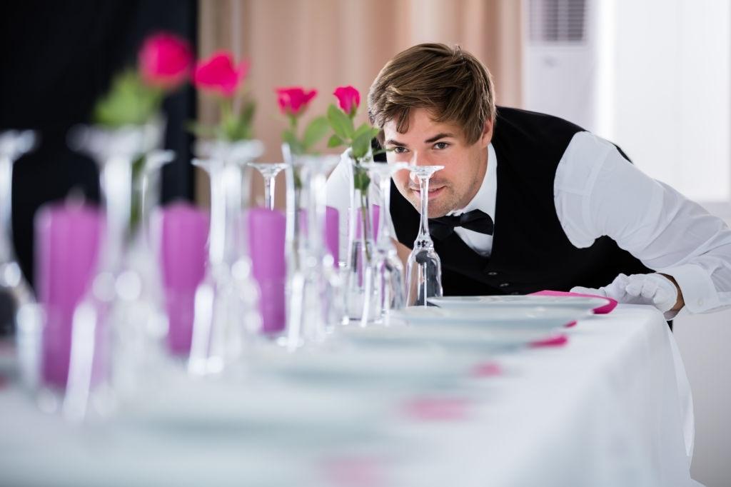 Handsome Waiter Looking At Wedding Table Arrangement At Restaurant