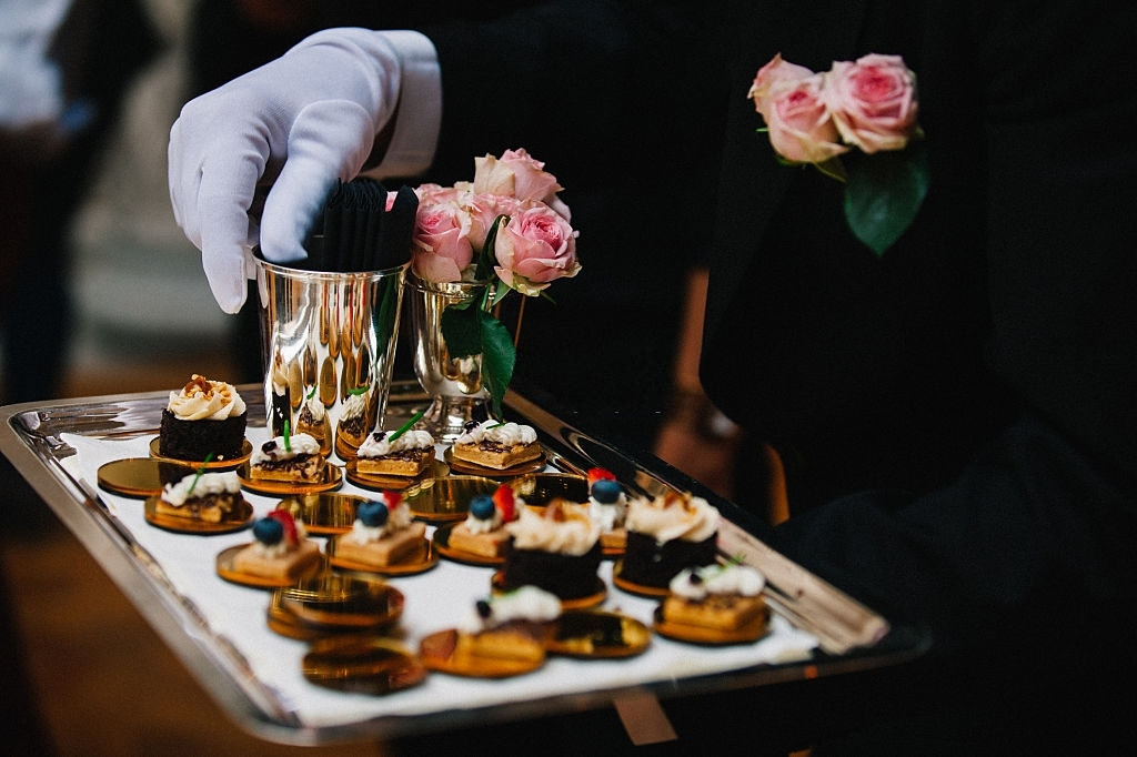 Professional caterer with white glove serve finger dessert foods during a cocktail wedding parties or events catering.
