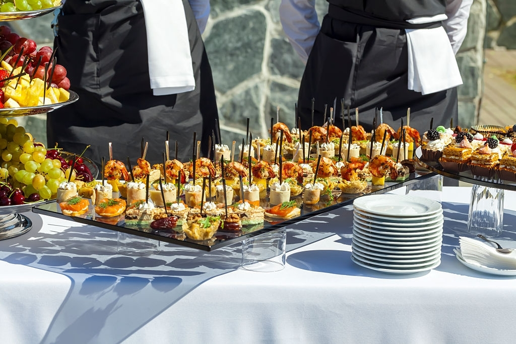 meat, fish, vegetable canapes on a festive wedding table outdoor