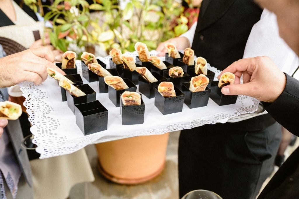 Tasty wedding appetizers served by waiters to the guests