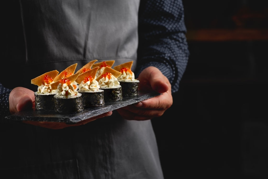 Sushi roll maki futo japanese food with with Rice for sushi, nori, avocado, salmon fillet, cheese, nachos, red caviar on black stone plate.